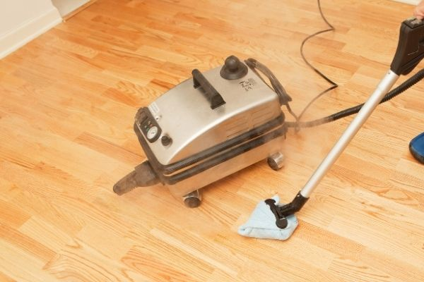 Person using steam cleaner with big water tank