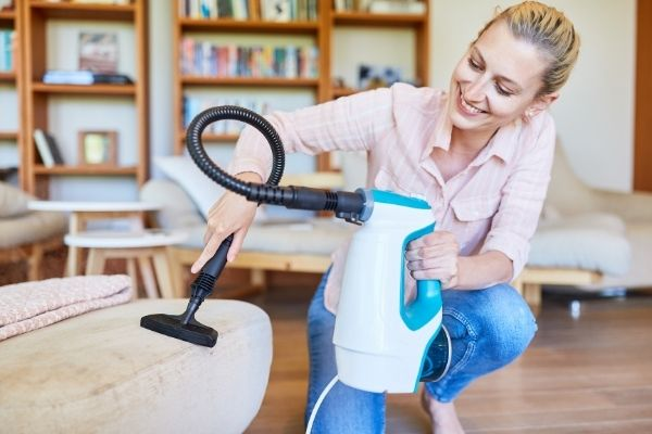 Woman using a portable upholstery cleaner
