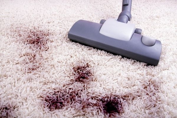 Vacuum cleaner on carpet with dark stains