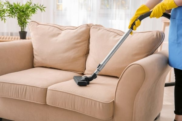 Person cleaning with corded upholstery cleaning machine