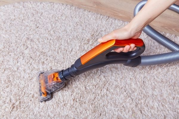 Person using handheld carpet cleaner