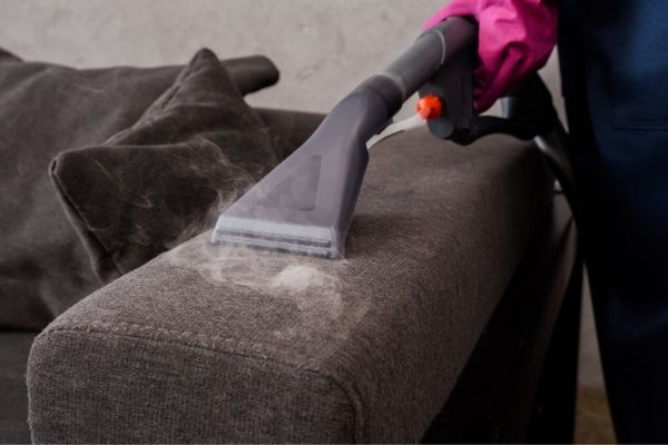 Person using vacuum and steam cleaner