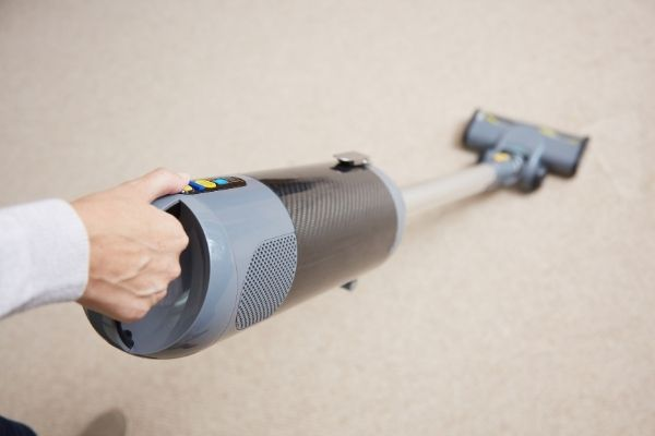 Person holding cordless vacuum steam cleaner