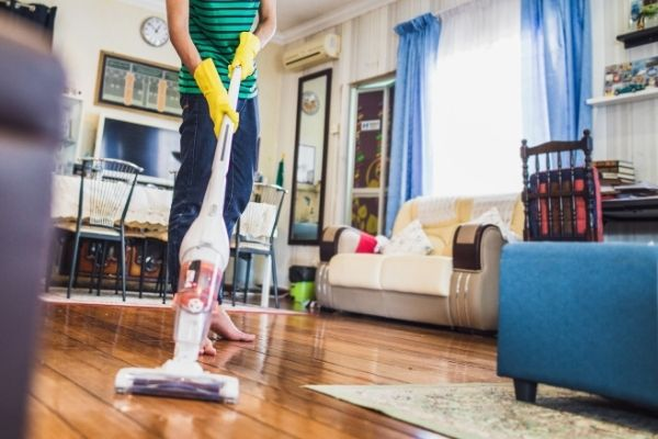 Person cleaning the living room with upright vacuum mop combo cleaner