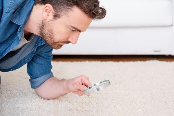 Man trying to look for dust mites on the carpet using a magnifier