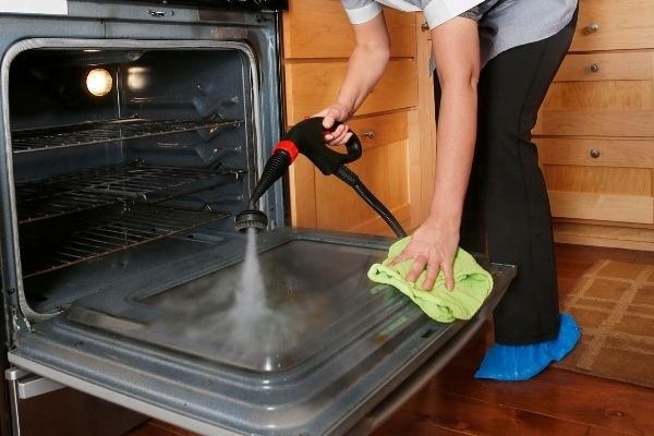 Person steam cleaning an oven