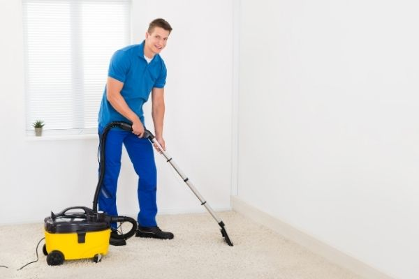 A male professional cleaner using a steam cleaner to clean carpet