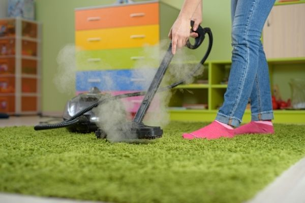 Woman cleaning green carpet with steam cleaner