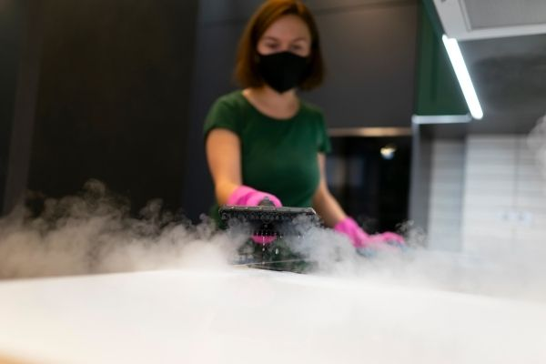 A woman steam cleans the kitchen